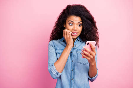 Portrait of frustrated girl use smartphone read social media information get dislike notification bite nails wear denim jeans shirt isolated over pink color background