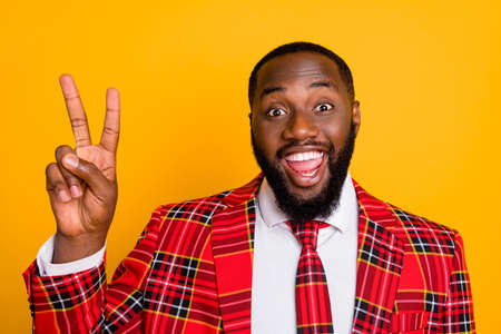 Hi there. Closeup photo of attractive funky dark skin guy good mood showing v-sign symbol wear checkered red costume blazer shirt tie isolated yellow color background