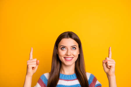 Close-up portrait of her she nice attractive pretty cute cheerful cheery confident girl pointing two forefingers up copy space ad advert isolated on bright vivid shine vibrant yellow color background