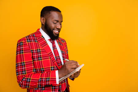 Photo of attractive attentive dark skin guy hold planner writing new startup project idea wear checkered red costume blazer shirt tie isolated yellow color background