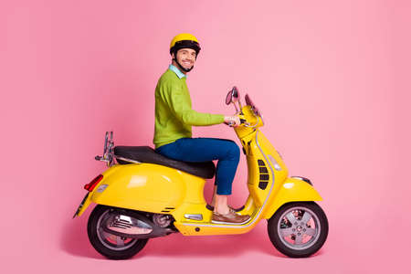 Profile side view portrait of his he nice attractive confident glad cheerful cheery guy riding moped traveling transport vehicle move isolated over pink pastel color background