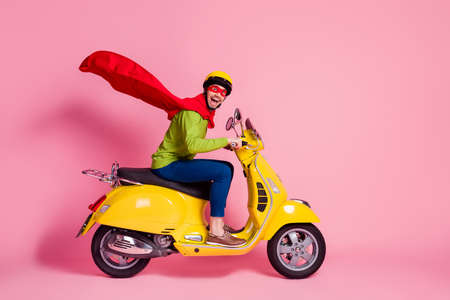 Profile side view of his he nice attractive, crazy overjoyed cheerful cheery guy driving moped fast speed wearing cape rescue safe planet isolated over pink pastel color background