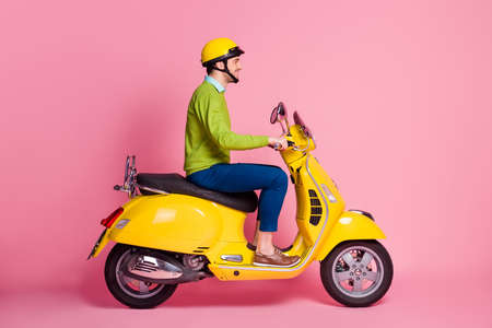 Profile side view portrait of his he nice attractive confident content cheerful cheery guy riding moped traveling license transport isolated over pink pastel color background