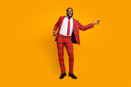 Full length photo of crazy funky dark skin guy dancing youth moves bachelor men stag party enjoy music wear plaid tartan red costume isolated bright yellow color background