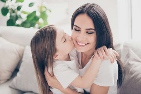 Closeup photo of pretty little girl kissing cheek young charming attractive mommy hugging holding each other close sitting comfy sofa spend time together home house indoors