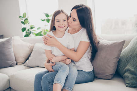 Photo of pretty little girl young charming mommy hugging holding each other close affectionate kissing daughter cheek sitting comfy sofa spend time together indoors home house