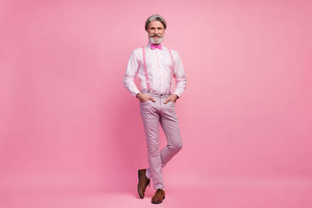 Full length body size view of his he nice attractive well-dressed imposing elegant cheerful cheery content grey-haired man holding hands in pockets isolated over pink pastel color background 写真素材