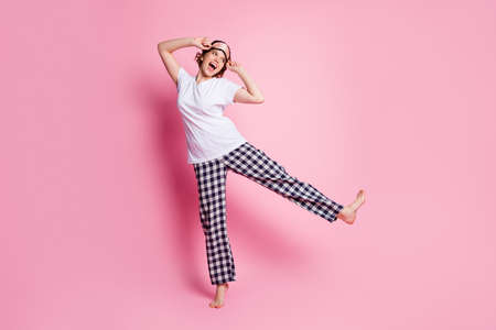 Full body photo of funny lady raise leg good mood slumber night party look side empty space wear sleep mask white t-shirt checkered pajama pants isolated pink color background