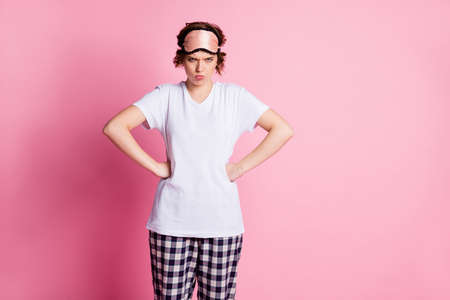 Photo of bad mood lady arms by sides displeased boyfriend early awakening angry wear sleeping mask white t-shirt plaid pajama trousers isolated pink color background