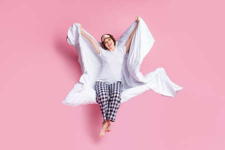 Full size photo of cheerful lady morning sit bed hold warm blanket under head stretching wake up wear mask white t-shirt plaid pajama pants barefoot isolated pink color background