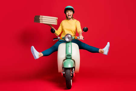 Portrait of her she nice attractive careless girlish cheerful cheery girl riding moped without legs having fun carrying pile stack bakery isolated on bright vivid shine vibrant red color background