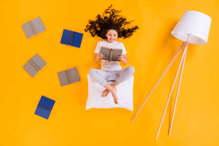 Full size high angle above flat lay view photo of little pupil lady lying floor morning reading sit on white pillow comfy wear pajama pants t-shirt isolated yellow color background