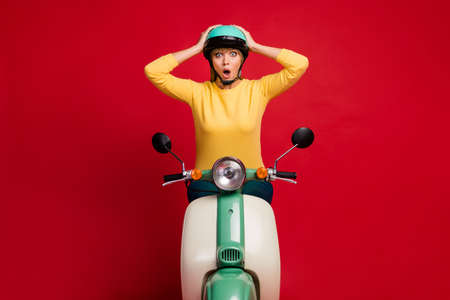 Portrait of her nice attractive lovely amazed cheerful overwhelmed girl sitting on moped great news reaction isolated on bright vivid shine vibrant red color background