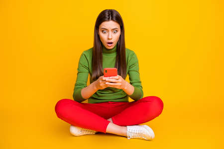 Oh no. Photo of beautiful lady sit floor holding telephone hands not believe eyes internet blog blocked wear green sweater red trousers isolated yellow color background 免版税图像