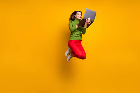 Full length photo of funny pretty lady jumping high holding using notebook modern technology wear casual green jumper red pants isolated yellow color background