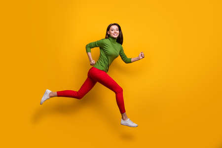 Full size photo of positive cheerful girl jump run fast after black friday sales wear casual style clothes white sneakers isolated over vibrant color background Stockfoto