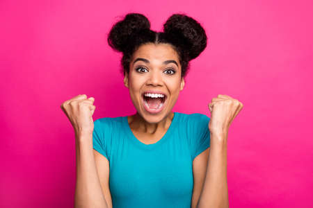 Closeup photo of crazy funky dark skin lady two buns raise fists celebrating amazing success achievement yelling loud wear blue casual t-shirt isolated bright pink color background 版權商用圖片