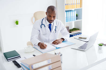 Photo of family doc dark skin successful professional guy write prescriptions big patients base journal wear white lab coat sit chair modern office clinic indoors