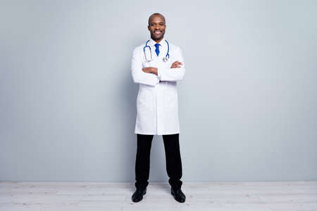 Full length photo of confident family doc dark skin guy meet patients virology clinic arms crossed friendly professional wear long lab coat tie pants shoes isolated grey color background Stock Photo