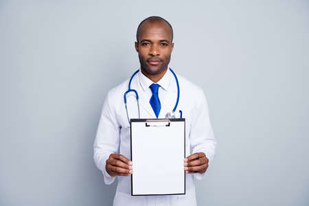 Photo of professional family doc dark skin guy hold clipboard prescription insurance pharmacy showing new medicine pills vitamins wear lab coat tie stethoscope isolated grey color background