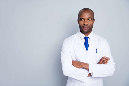 Photo of curious doctor dark skin guy virologist agent corona virus arms crossed pandemic virus expert look empty space interested wear white lab coat tie isolated grey color background