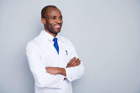 Zdjęcie wesoły lekarz ciemna skóra facet wirusolog agent korona wirus seminarium konferencja słuchać koledzy badania ramiona skrzyżowane nosić biały fartuch laboratoryjny krawat na białym tle szary kolor tło