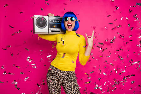 Photo of crazy festive lady rocker party confetti fall vintage recorder on shoulder show horns wear specs yellow turtleneck blue wig leopard pants isolated bright pink color background Stockfoto