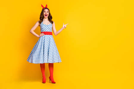 Full size photo excited surprised crazy girl promoter point index finger copyspace direct way adverts promo wear headband stockings high-heels stilettos isolated bright shine color background