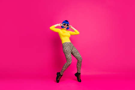 Full size photo of funny lady dance student party v-sign symbols near eyes wear specs yellow turtleneck blue wig boots leopard trousers isolated bright pink color background