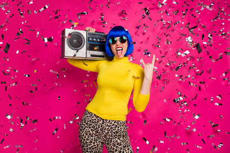 Photo of crazy lady rocker party confetti fall vintage recorder on shoulder show horns stick tongue wear specs yellow turtleneck blue wig leopard pants isolated bright pink color background Stockfoto