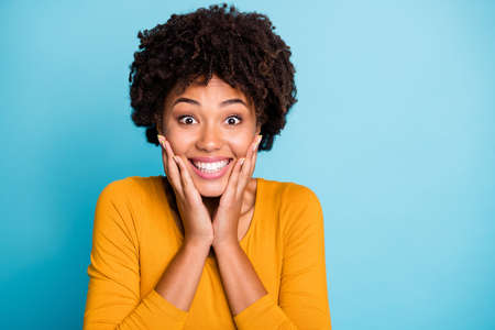 Omg i cant believe. Close up photo enthusiastic cheerful afro american girl wait long expected wish present touch hands face wear style stylish trendy sweater isolated blue color background