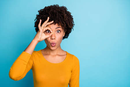 Portrait of astonished crazy afro american girl make okay sign binocular eye watch her neighbors impressed stare stupor wear bright pullover isolated over blue color background Archivio Fotografico