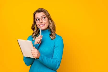 Photo of attractive business lady curly hairdo hold paper personal planner writing new novel chapter inspired look up wear specs blue turtleneck isolated bright yellow color background