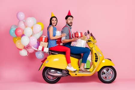 Full length photo crazy positive energetic two people buddies drive yellow retro motor bike hold gift boxes have air balloons fly wear cone shirt red trousers isolated pink color background