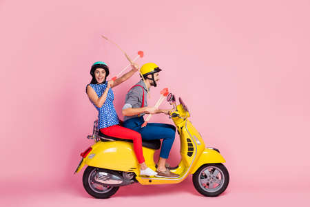 Full length profile side photo crazy two people biker amour motorcyclist riders drive yello0w motor bike fast speed on 14-february trip shoot arrow red hearts isolated pink color background