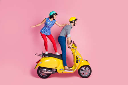 Full size profile side photo of careless cheerful wife husband extreme sport motorcyclist ride yellow chopper electric scooter stand look distance road isolated over pastel color background