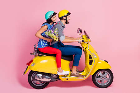 Full length profile side photo of positive cheerful bikers driver rider two people drive motor bike enjoy journey woman hold carry wildflowers bouquet isolated pastel color background