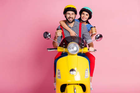 Portrait of nice attractive cheerful cheery glad couple driving moped drinking latte cappuccino having fun isolated over pink pastel color background