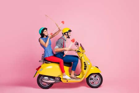 Photo de côté de profil complet du corps d'amours positifs deux personnes voyagent voyage sur une femme rapide chopper jaune s'asseoir tirer flèche dans le ciel porter une tenue de style décontracté isolé fond de couleur rose pastel