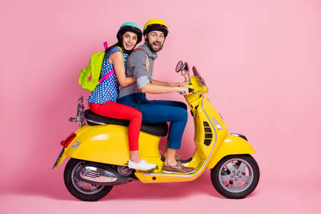 Profile side view of his he her she nice attractive cheerful cheery amazed couple driving moped having fun spending vacation holiday adventure summer sale isolated over pink pastel color background