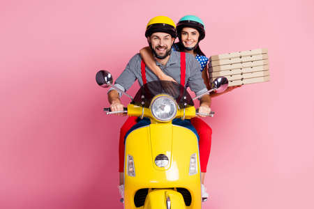 Portrait of attractive cheerful cheery careful couple driving moped carrying pizza pies home snack meal dinner isolated over pink pastel color background
