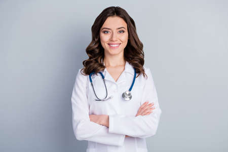Photo of attractive family doc lady patients consultation beaming friendly smiling reliable virology clinic arms crossed wear white lab coat stethoscope isolated grey color background