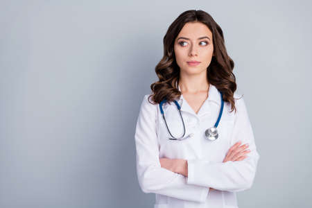Photo of attractive family doc lady arms crossed patients consultation not smiling virology clinic look side empty space wear white lab coat stethoscope isolated grey color background