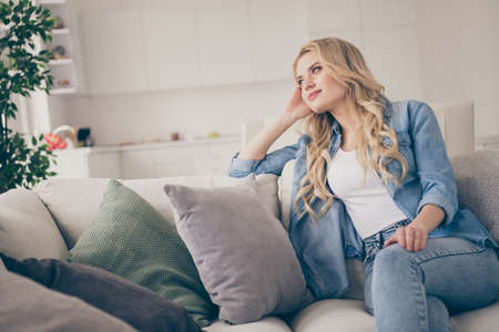 Photo of domestic pretty charming blond lady relaxing sit comfy couch staying home good mood lean head on hand dreamer quarantine time lighted living room indoors