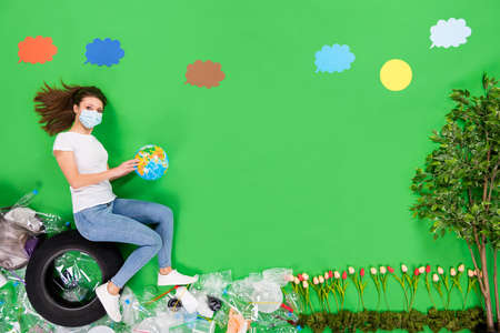 High angle flat lay photo activist lady grow flowers take care nature sort plastic hold earth globe wear mask breathe toxic polluted air isolated green color background Foto de archivo