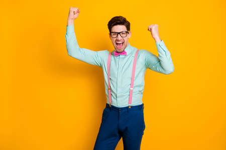 Portrait of positive man cheering with raise fists scream yeah isolated over bright shine color background Stok Fotoğraf