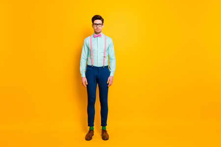 Full length photo of handsome cool clothes guy boyfriend stand self-confidently not smiling wear specs shirt suspenders bow tie trousers shoes socks isolated bright yellow color background 写真素材