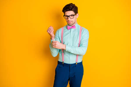Photo of handsome cool clothes young guy boyfriend look empty space seriously buttoning shirt sleeve wear specs teal shirt pink suspenders bow tie trousers isolated yellow color background Foto de archivo