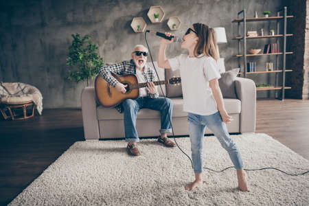 Photo of grandpa sit sofa play guitar little pretty granddaughter hold mic singing song spend time together cool trendy sun glasses stay home quarantine rejoicing modern living room indoors