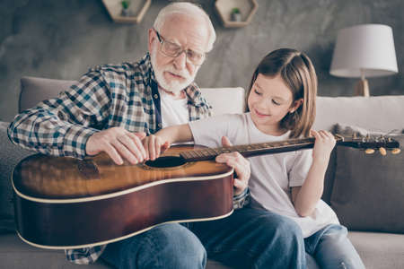 Photo of funny aged old grandpa little pretty granddaughter holding playing guitar teaching small princess bonding spend stay home quarantine useful time modern interior living room indoors